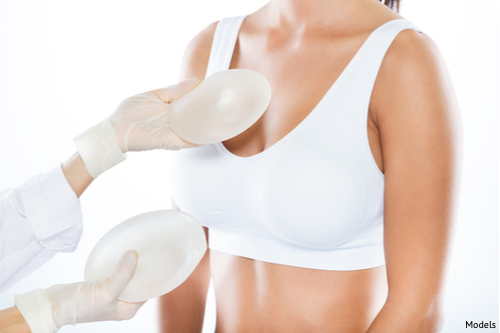 Woman considering her breast implant options during a breast augmentation consultation.